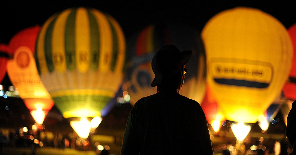A spectator watches the hot air balloon night glow during the 32nd Bristol International Balloon Fiesta at the Ashton Court Estate in Bristol on August 12, 2010.</p>