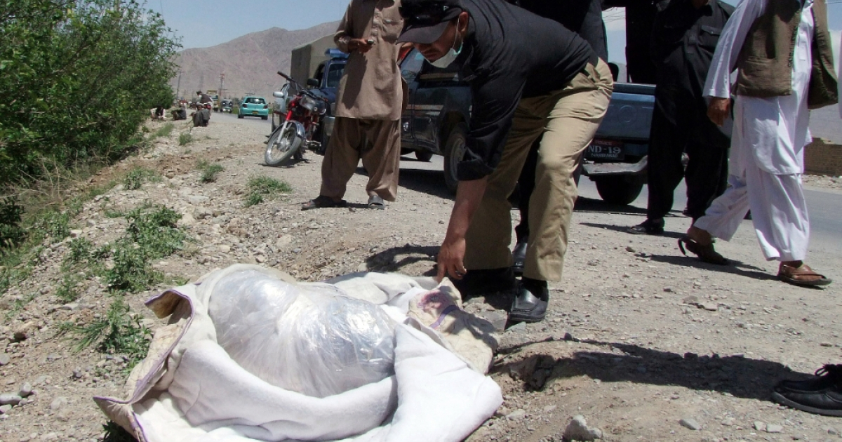 A Pakistani police official looks at the covered dead body of British aid worker Khalil Rasjed Dale (L), found on a road side in Quetta on April 29, 2012.</p>