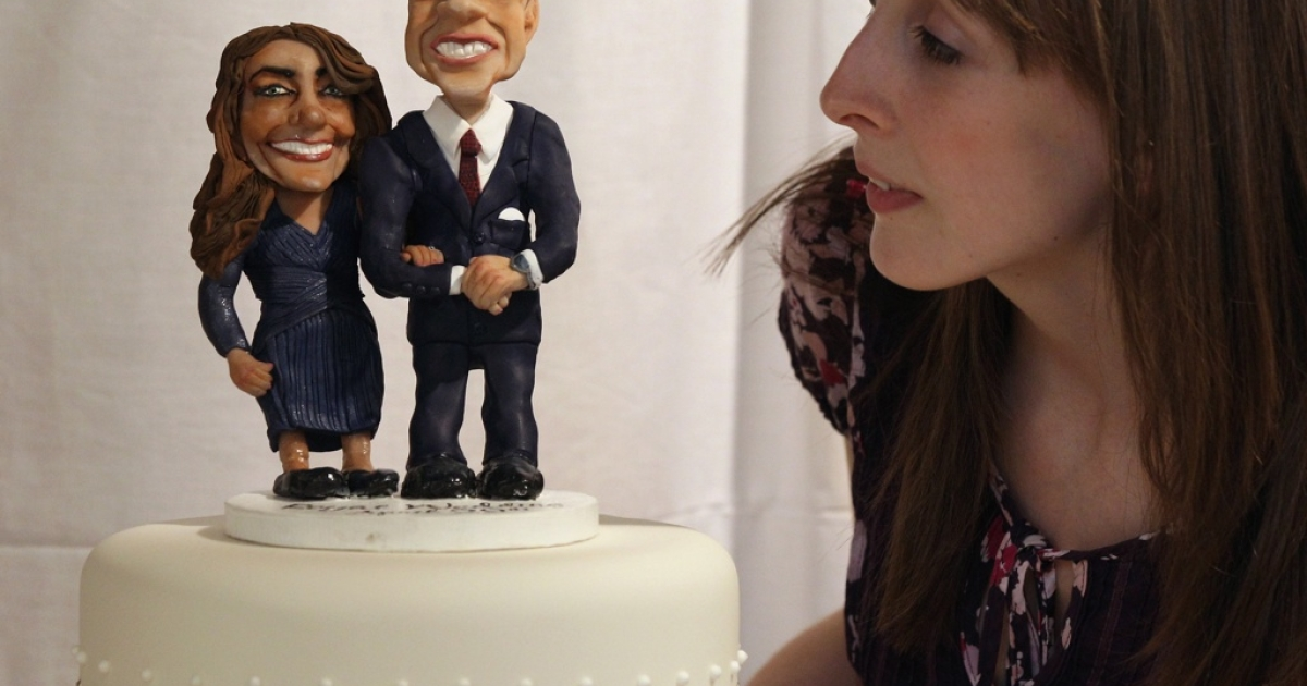 A woman admires a cake featuring figures of Prince William and Kate Middleton at an exhibition of Royal Wedding cakes on April 21, 2011 in London, England. The cake features in the 'Let Them Eat Cake' exhibition inside Wellington Arch on Hyde Park Corner.</p>