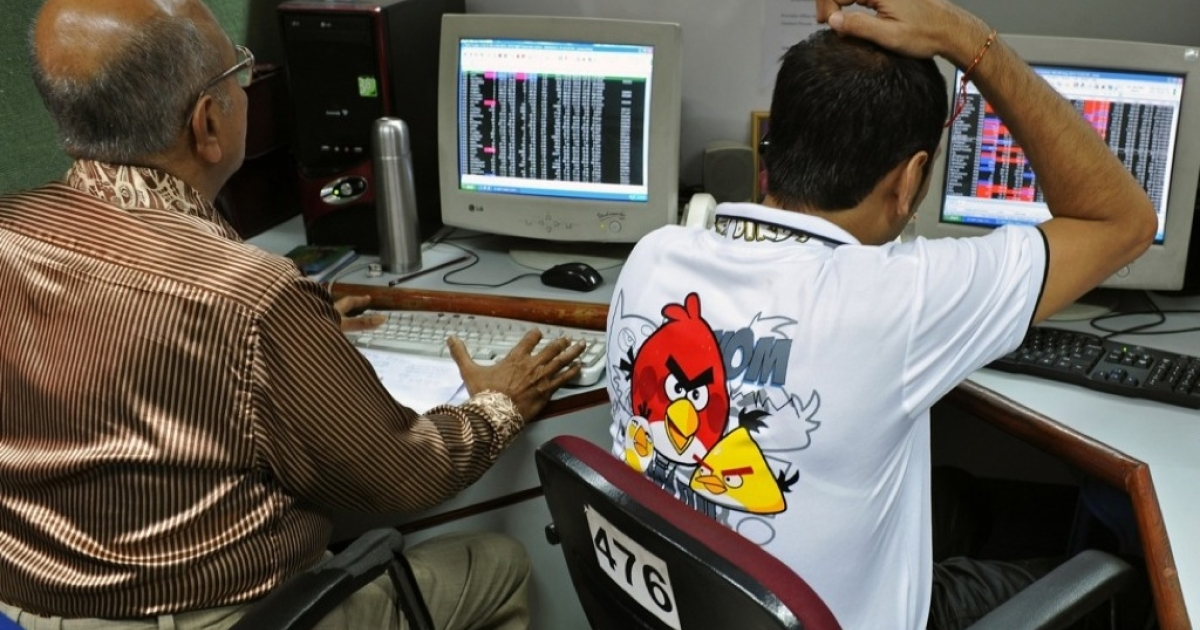 Indian stock dealers keep a watch on share prices at the Bangalore Stock Exchange (BgSE) on August 8, 2012.</p>