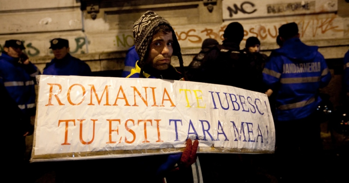 For two weeks, protesters across Romania have been gathering in groups of a few dozen to to a few thousand to show their displeasure with the ruling party of President Traian Basescu. A protestor holds a sign reading