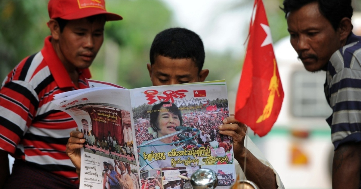 Men read a newspaper carrying a picture of Myanmar opposition leader Aung San Suu Kyi on its front-page a day after parliamentary by-elections across the country, in Yangon on April 2, 2012. Suu Kyi hailed a 'new era' for Myanmar and called for a show of political unity after her party claimed a major victory in landmark by-elections.</p>