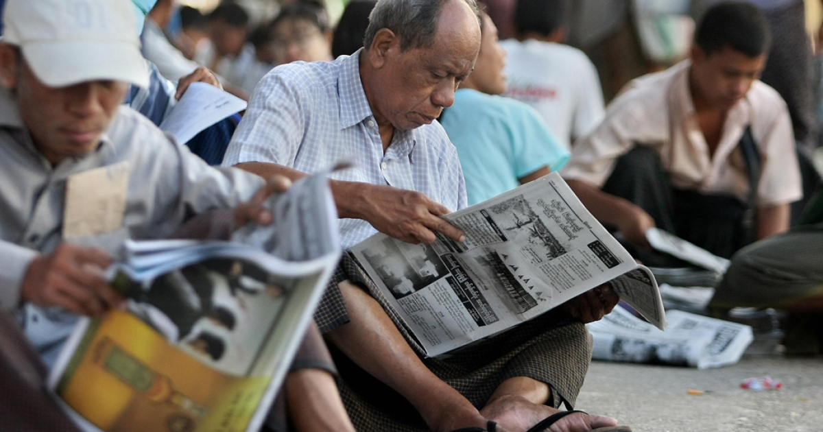 Burmese read newspapers on the street in Rangoon on May 22, 2009.</p>