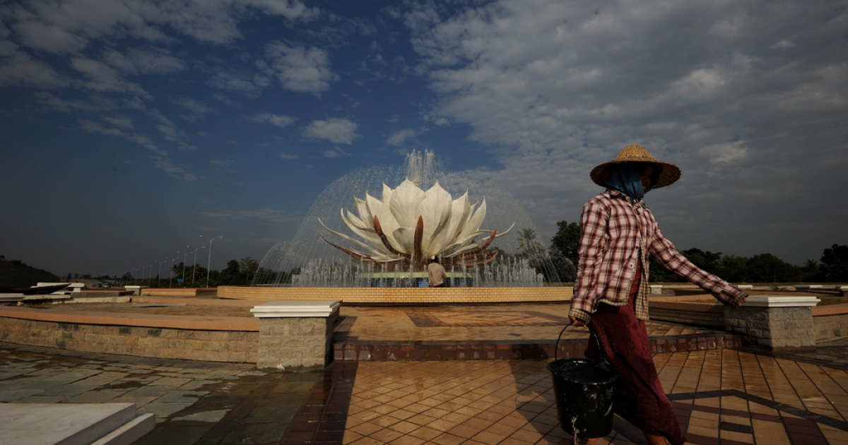 A Burmese worker walks past a water fountain in Naypyidaw on Jan. 30, 2011 as the country's capital prepares for the opening of the national parliament.</p>