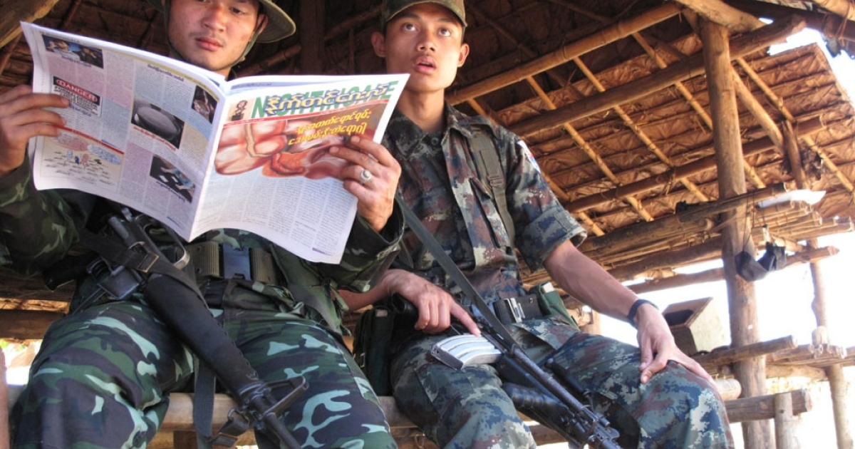 Soldiers in the Karen National Liberation Army share a newspaper at an outpost in Burma on Feb. 22, 2012. The ethnic militia, which controls vast stretches of eastern Burma, has insisted that Burma's army must withdraw all troops from its claimed territory before it can proceed with a cease-fire. The conflict between the Karen tribe and Burma's army is the world's longest-running civil war.</p>