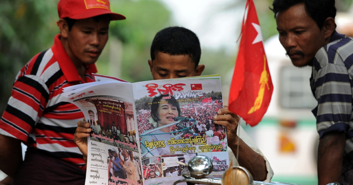 This file picture taken on April 2, 2012 in Yangon shows men reading a newspaper carrying a picture of Myanmar opposition leader Aung San Suu Kyi on its front-page a day after parliamentary by-elections across the country.</p>