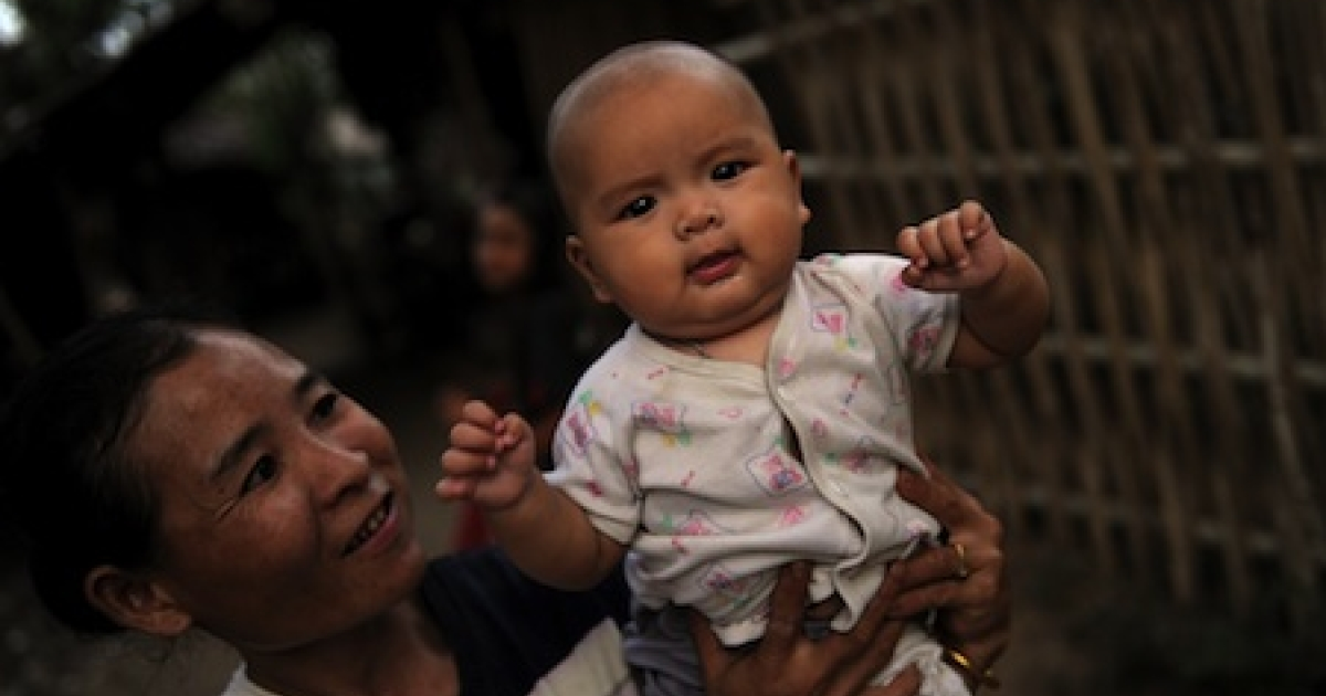 An ethnic Karen refugee holds a baby at Mae La camp on the Thai-Burma border. The camp, which houses ethnic minorities fleeing war in Burma, is among Southeast Asia's largest.</p>