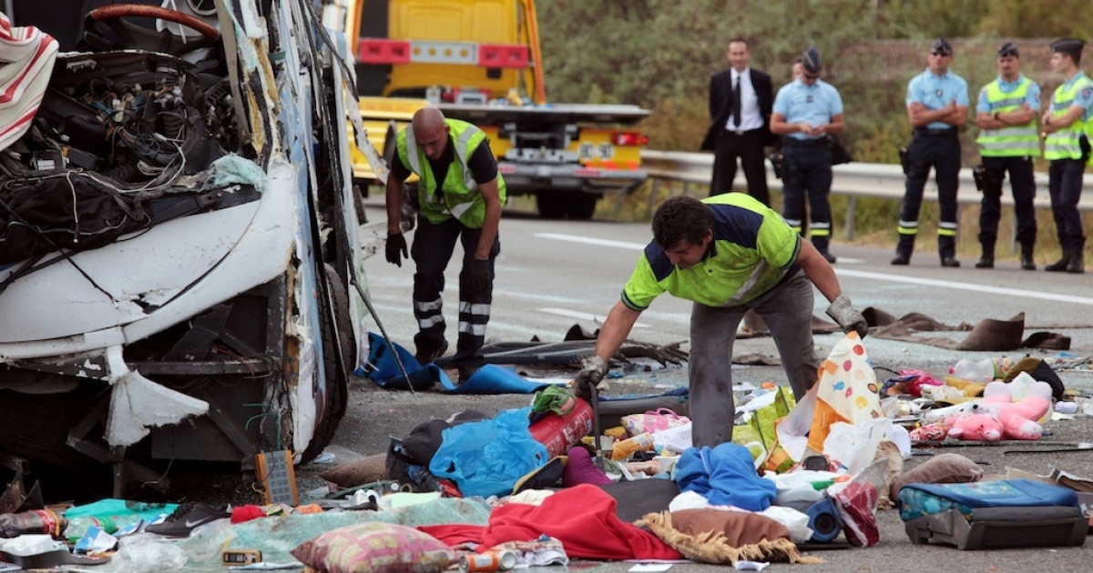 A tour bus crashed in southern California late Sunday, leaving at least eight people dead as authorities continue to clear the crash site. Here, French highway service workers remove belongings from the ground before towing a bus out of the road, on September 2, 2012, after it crashed earlier along the A8 highway cear the southern French city of Vidauban.</p>