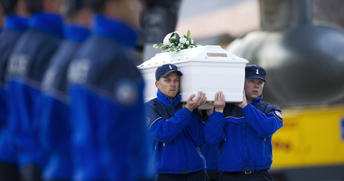 Police officers carry the coffin of one of the 28 victims of Sierre's coach crash to load it into a Belgian military cargo aircraft  at Sion airport on March 16, 2012 in Switzerland. The accident occurred when a school bus carrying 11 -12 year old children back to Belgium from a skiing holiday, crashed into a tunnel wall, killing 28 of the 52 passengers. Belgium is holding a day of national mourning today to remember the victims of the crash.</p>