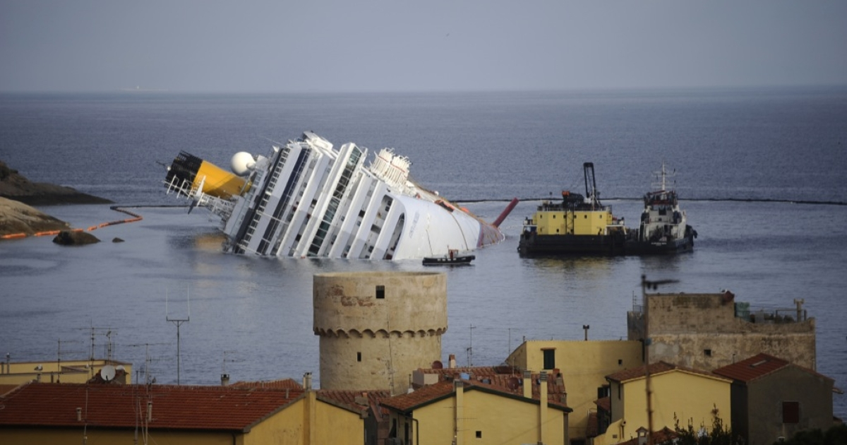 The stricken cruise liner Costa Concordia (background) is seen from the village while lying aground in front of the Isola del Giglio (Giglio island) on Jan. 23, 2012 after hitting underwater rocks on Jan. 13.</p>