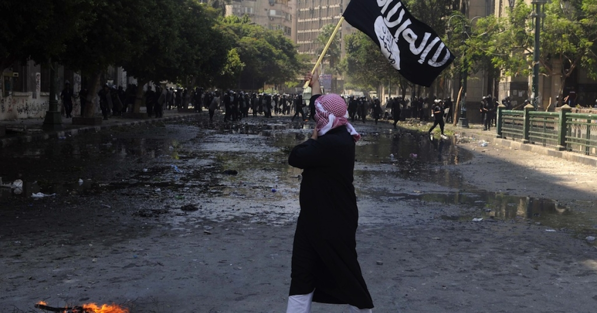 An Egyptian protester holds an Al-Qaeda affiliated flag in front of the riot police near the US embassy in Cairo on September 14, 2012 against a film mocking Islam. Just a few young protesters pelt rocks randomly, with no response from police as the clashes subsided after Egypt's Muslim Brotherhood withdrew calls for nationwide protests, saying they would instead participate in a 'symbolic' demonstration.</p>