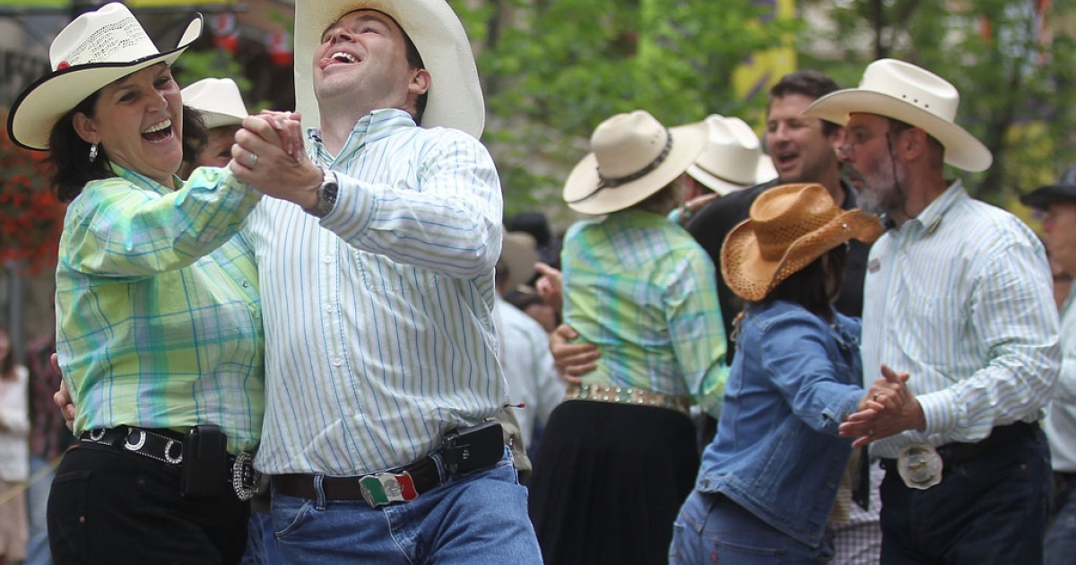 Revelers square dance during the Calgary Stampede on July 11, 2011, in Calgary, Alberta, Canada. The 10-day event, drawing over 1 million visitors, is Canada's largest annual rodeo and is billed as the Greatest Outdoor Show on Earth.</p>