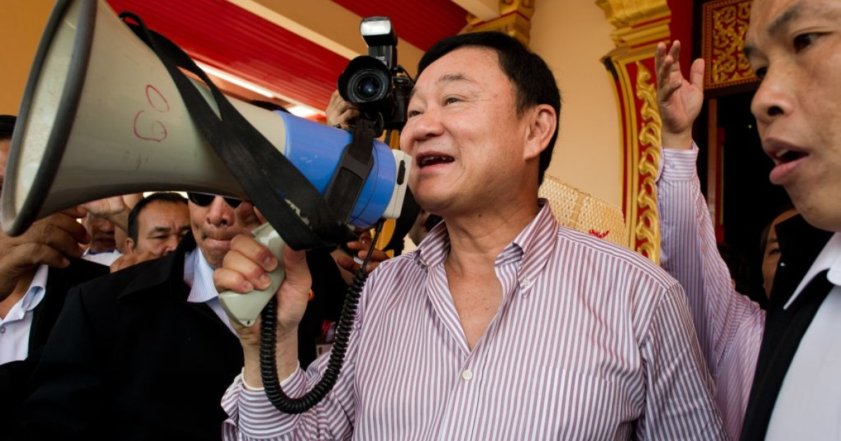 Former Thai prime minister Thaksin Shinawatra speaks to his supporters at the That Luang Stupa during a visit to the Laos capital Vientiane on Apr. 12, 2012. Thousands more Red Shirt supporters are expected to attend his follow-up rally in the Cambodian tourist town of Siem Reap.</p>