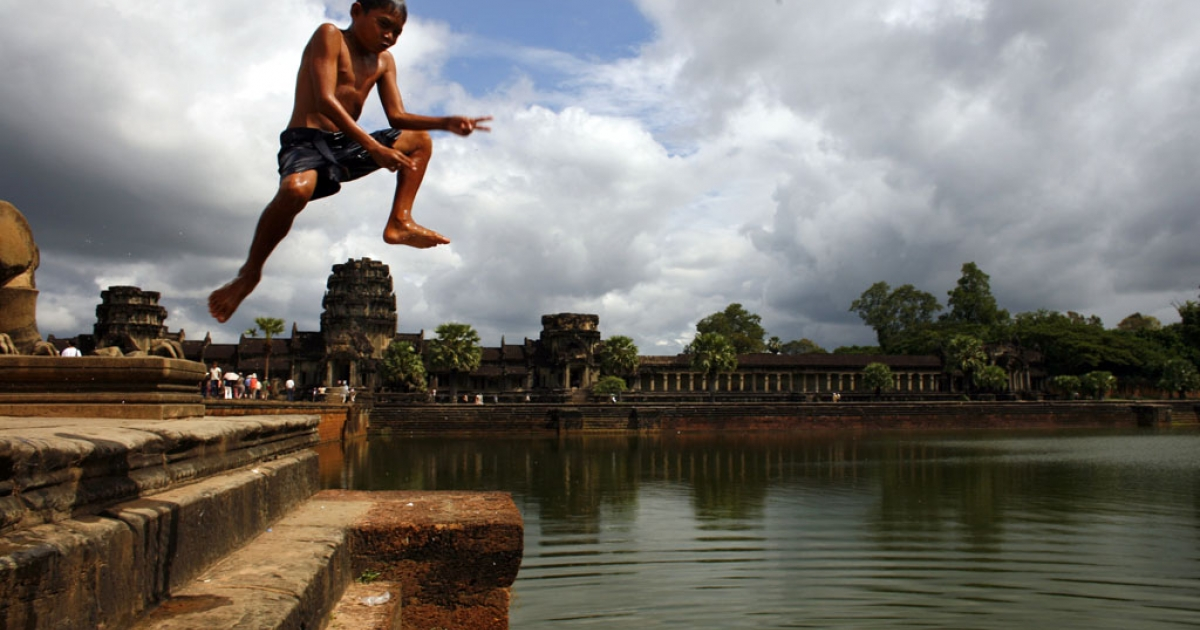 A Cambodian boy cools off by jumping into the waters on the grounds of the Angkor Wat temple in Siem Reap, Cambodia.</p>