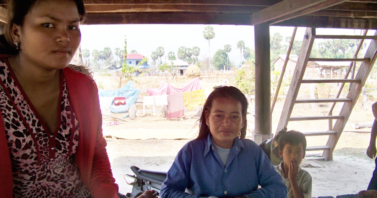 "Pah Eang, 22 (left), and Nith Pov, 29 (right), sit underneath their new house, which has become a gathering place for the remaining family members of two accused ""sorcerers"" who were killed in this remote village six months ago.</p>"