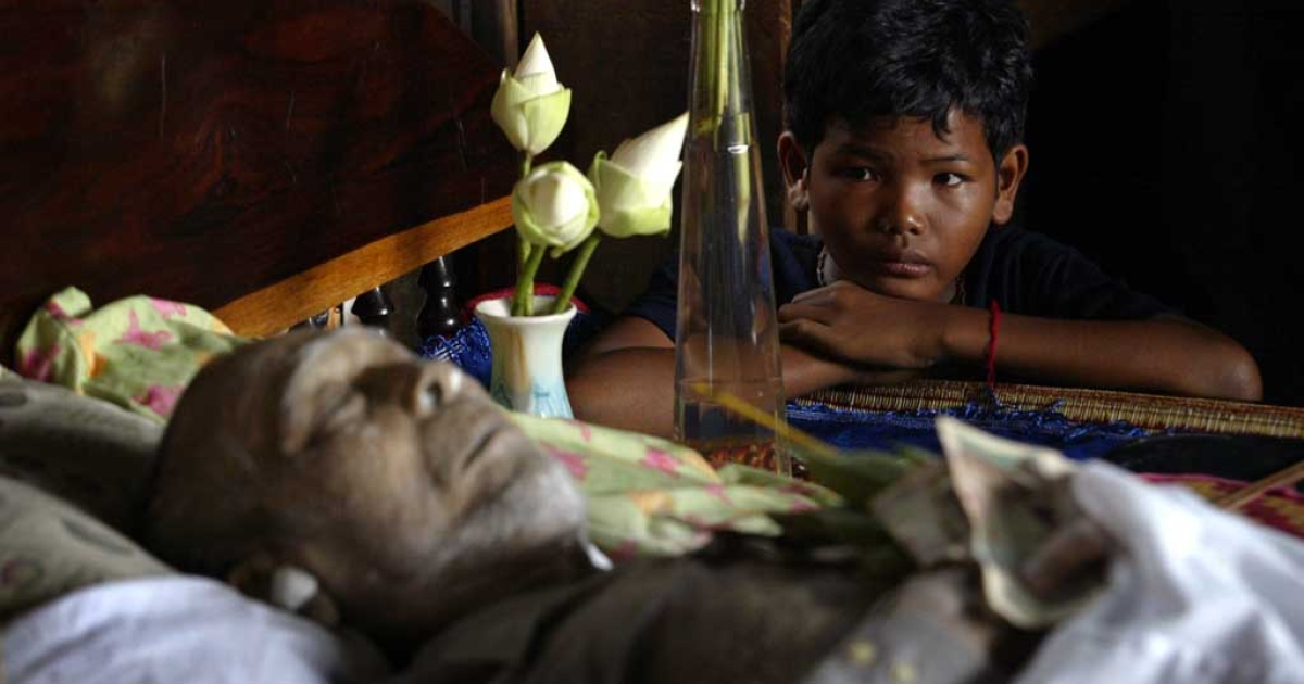 A young boy sits next to the body of former Khmer Rouge military chief Ta Mok in Anlong Veng, Cambodia, July 22, 2006.</p>