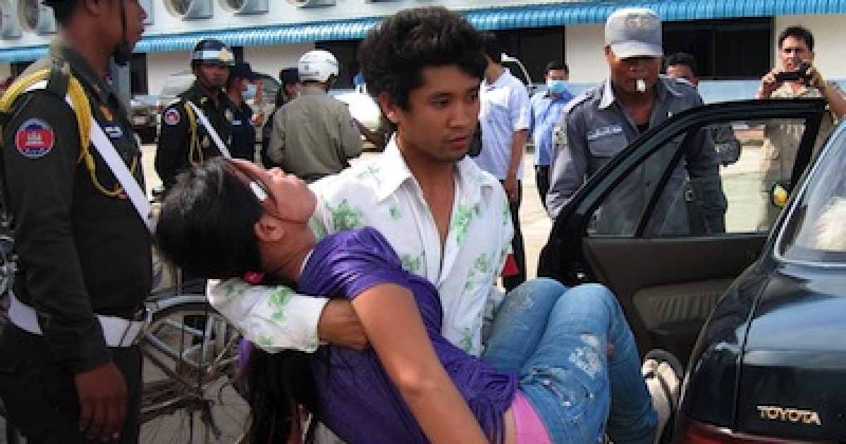 A Cambodian man carries an unconscious woman from a factory in Phnom Penh on October 12, 2009. Cambodia's garment industry is the impoverished nation's largest source of income, providing 80 percent of its foreign exchange earnings and employing an estimated 350,000 people.</p>