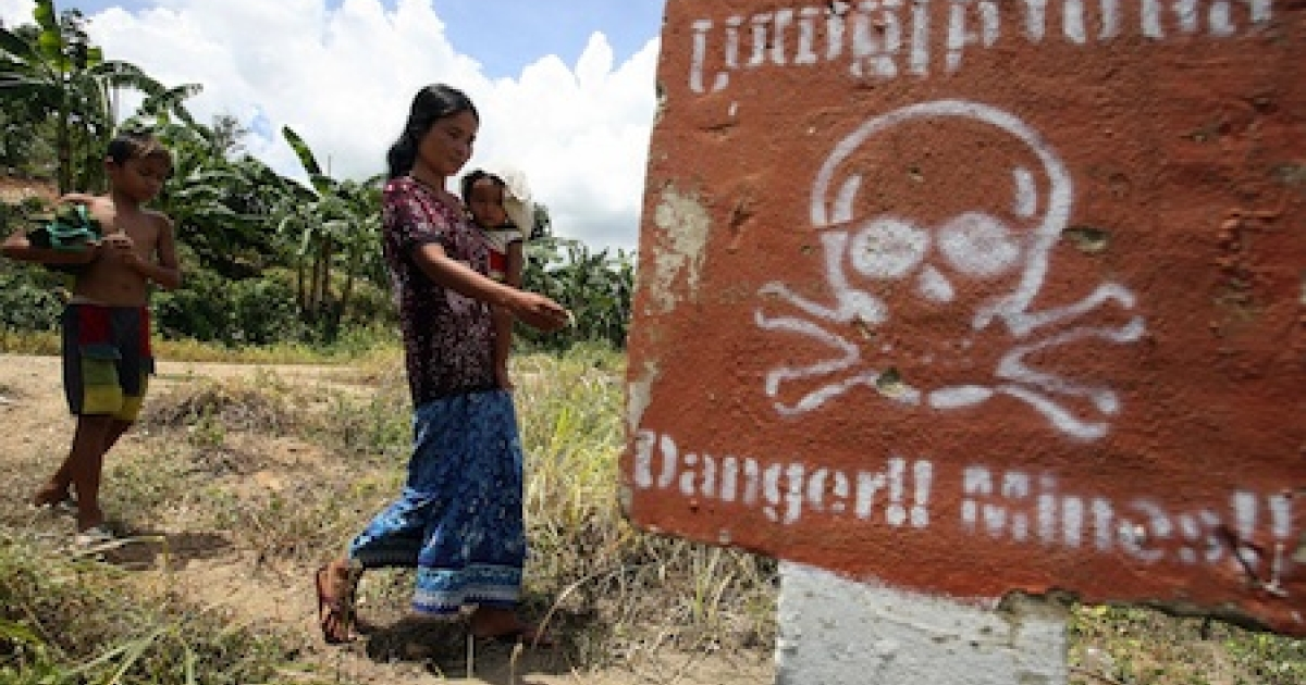 A Cambodian woman carrying a baby walks by a land mine awareness sign in the former Khmer Rouge's stronghold Pailin near the Thai border some 375 kilometers north west of the capital, Phnom Penh, in 2007.</p>