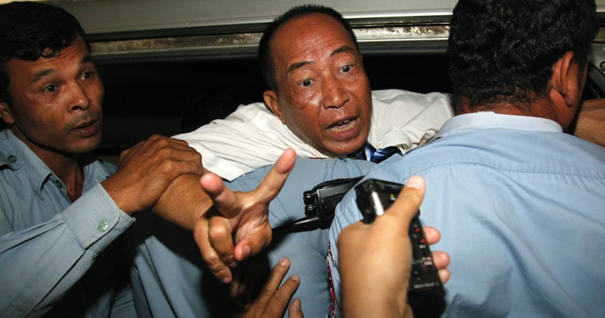 Mam Sonando (C), owner of the independent Beehive radio station gestures as police officials escort him into a car after his verdict at the Phnom Penh municipal court on October 1, 2012. A prominent critic of Cambodia's government was sentenced to 20 years in prison on October 1 for an alleged secessionist plot, dismaying rights campaigners who decried the verdict as politically motivated.</p>