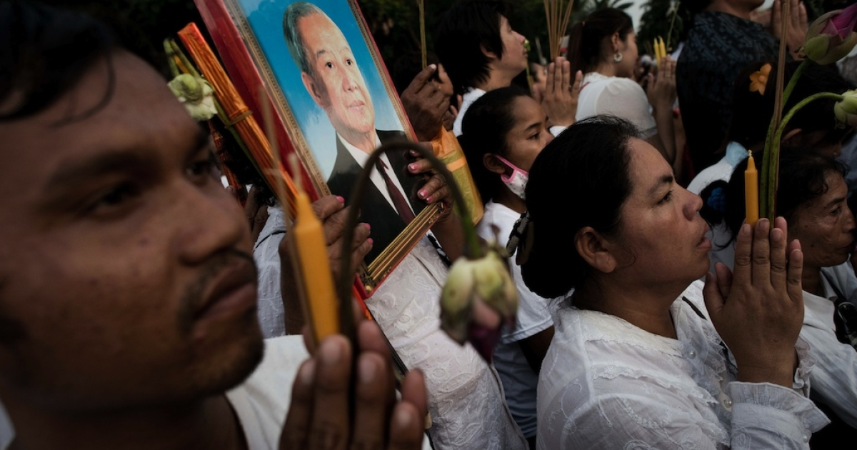 Cambodian people pray as the convoy transporting the coffin of late former king Norodom Sihanouk passes by in front of the Royal Palace in Phnom Penh on October 17, 2012. Tens of thousands of mourners lined the streets of the Cambodian capital on October 17 to pay their last respects to revered former king Norodom Sihanouk on his final journey home from China.</p>