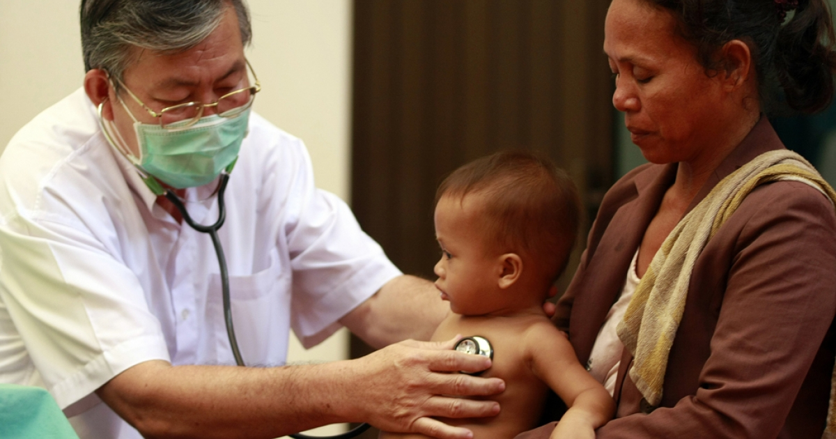 This photo taken on July 5, 2012 shows a Cambodian doctor (L) checking a child (C) at Kantha Bopha children's hospital in Phnom Penh.</p>