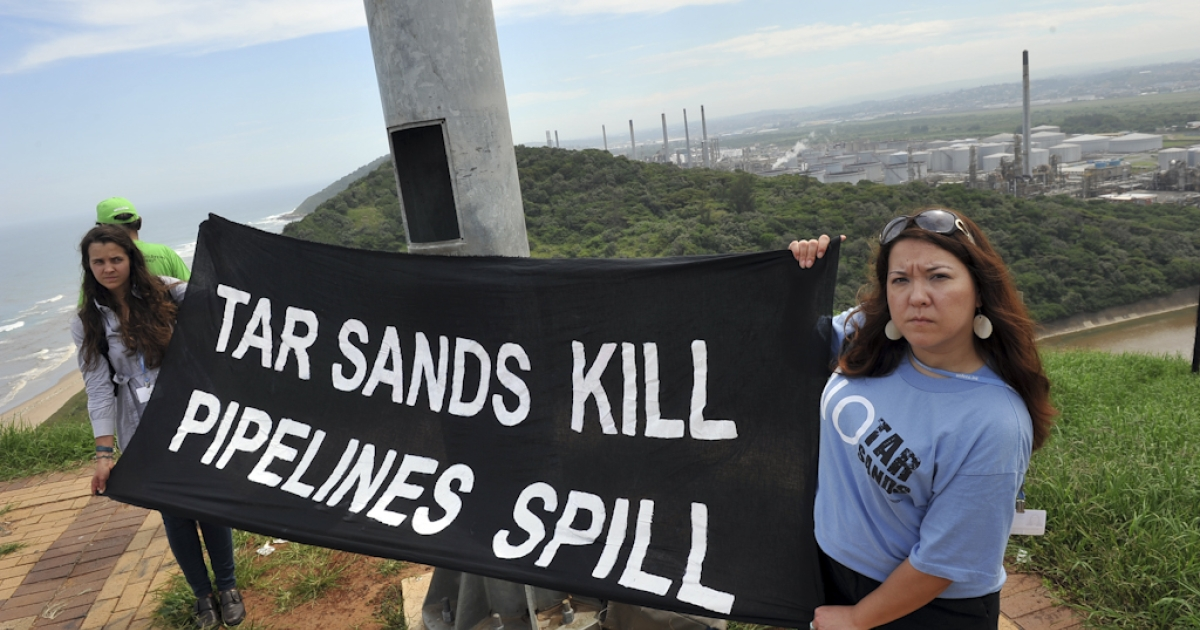 People protest outside the a South African oil refinery in Durban on November 30, 2011 calling on the Canadian government to stop actively promoting tar sands development projects and to stop ignoring international commitments Canada has made to cut greenhouse gas emissions.</p>