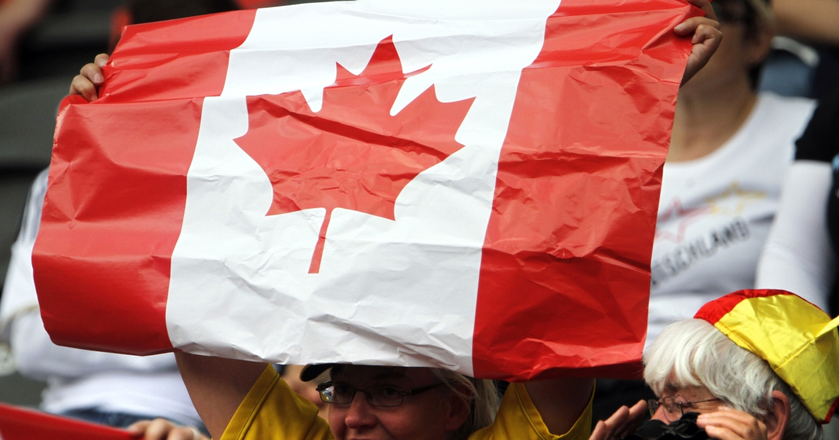 Canada fans cheer with their national flag before the opening match of the FIFA women's soccer World Cup Germany vs Canada at Berlin's Olympic Stadium on June 26, 2011.</p>