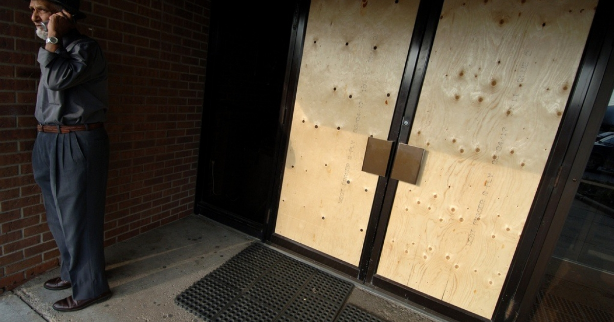 The caretaker for the International Muslims Organization mosque in Toronto stands in the boarded up entrance way to the mosque on June 4, 2006. The mosque was vandalized in the wake of multiple terror arrests in Toronto.</p>