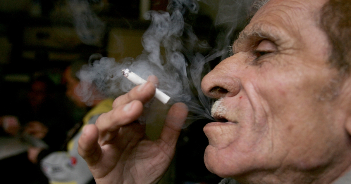 A Palestinian man smokes a cigarette inside his shop in the old town in the West Bank city of Jenin on Friday.</p>