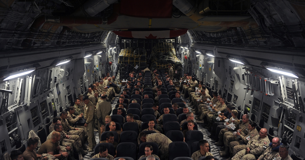 Canadian soldiers sit aboard a plane on their way home at Kandahar airbase on July 5, 2011.</p>