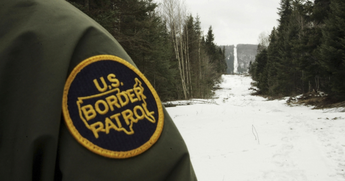A U.S. Border Patrol agent stands along the boundary marker cut into the forest marking the line between Canadian territory on the right and the United States near Beecher Falls, Vermont.</p>