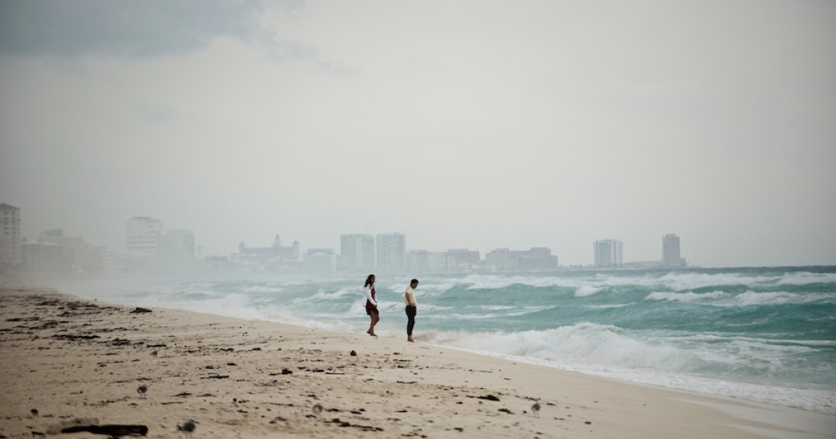 A couple walks along Playa del Carmen beach near Cancun on October 25, 2011.</p>