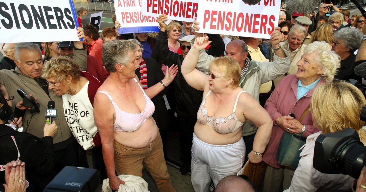 Two elderly women take off their tops as hundreds of retirees disrupted traffic in Melbourne's city center in a protest against the Australian government's lack of support for seniors in the federal budget.</p>