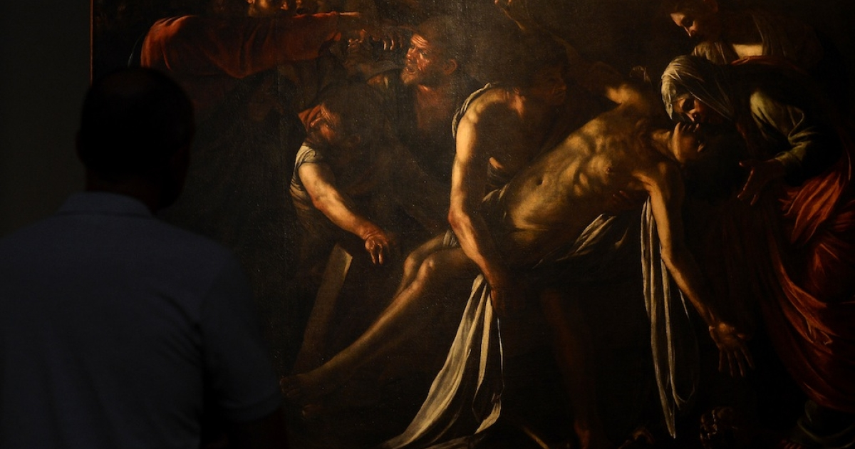 A man stands in front of the restored Caravaggio painting 'Resurrection of Lazarus' at the Palazzo Braschi museum in Rome on June 15, 2012.</p>
