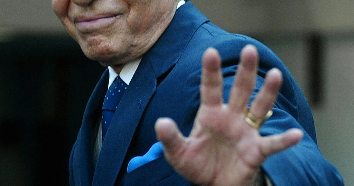 Argentina's former president Carlos Menem waves at the press after taping an interview for a Chilean TV programme in Santiago, Chile, on September 9, 2004.</p>