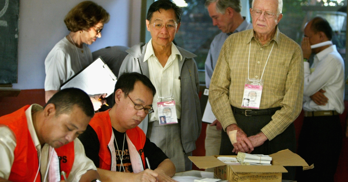 Former US President Jimmy Carter, right, watches election workers in Jakarta, Indonesia during a visit to a polling station on July 5, 2004.</p>