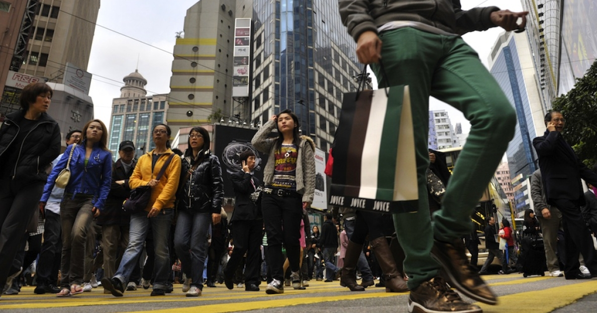 Shoppers cross a road in Causeway Bay where retail real estate is more expensive than New York's Fifth Avenue.</p>