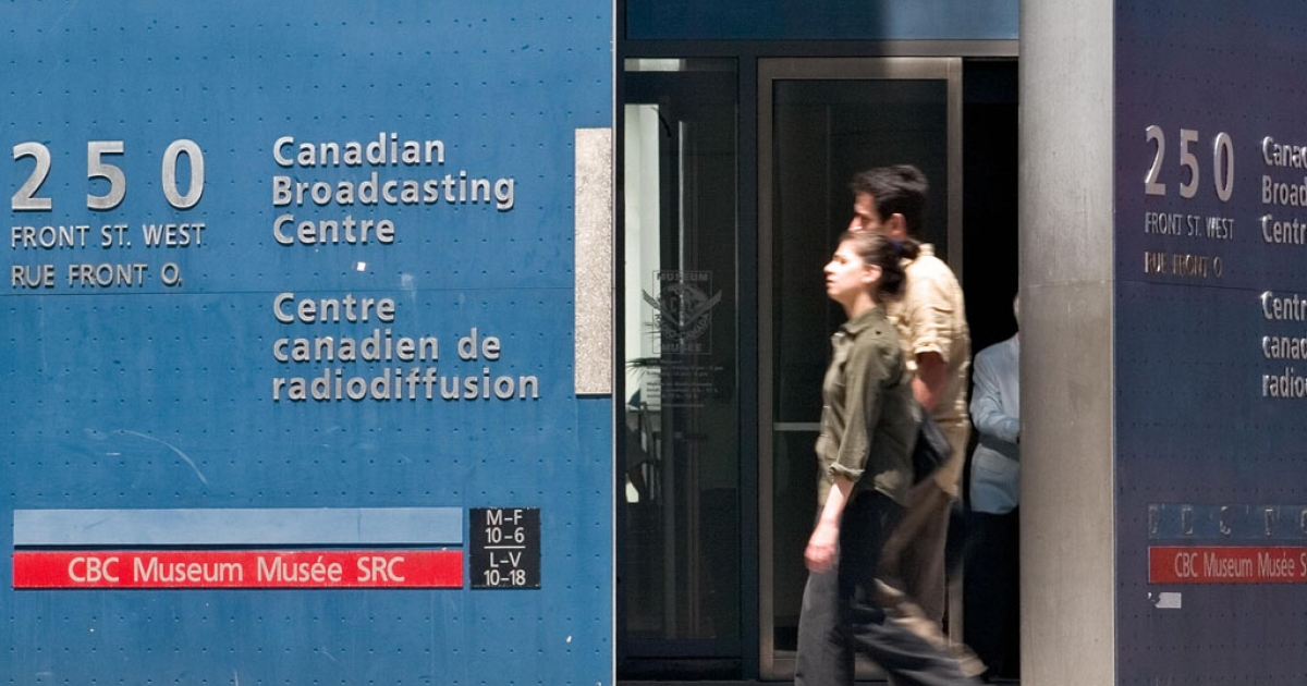 Pedestrians walk past the CBC building in Toronto. CBC is cutting 650 jobs and reducing original programming in an effort to absorb government budget reductions.</p>