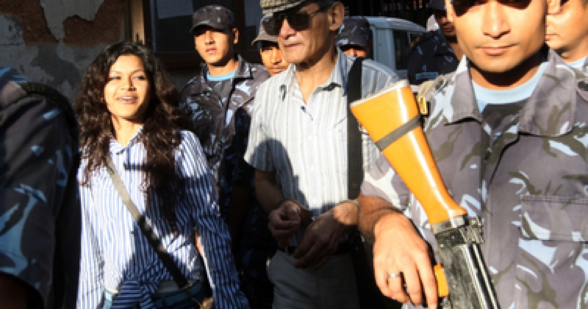 Nepalese police guide alleged French serial killer Charles Sobhraj (center) and his wife Nihita Biswas (left) towards a waiting vehicle after a court hearing in Kathmandu. The 22-year-old Biswas, who claims to have married 67-year-old Charles Sobhraj in a secret ceremony while he serves a life sentence in Nepal, appeared in India's hugely popular reality television show