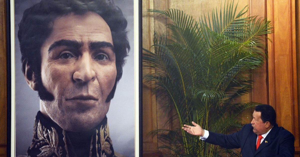 Venezuelan President Hugo Chavez (R) shows a picture of the possible face of Liberator Simon Bolivar — a digital rendering from genetic data, following the exumation of Bolivar remains in 2010 — during celebrations of Bolivar's birthday in Caracas on July 24, 2012.</p>
