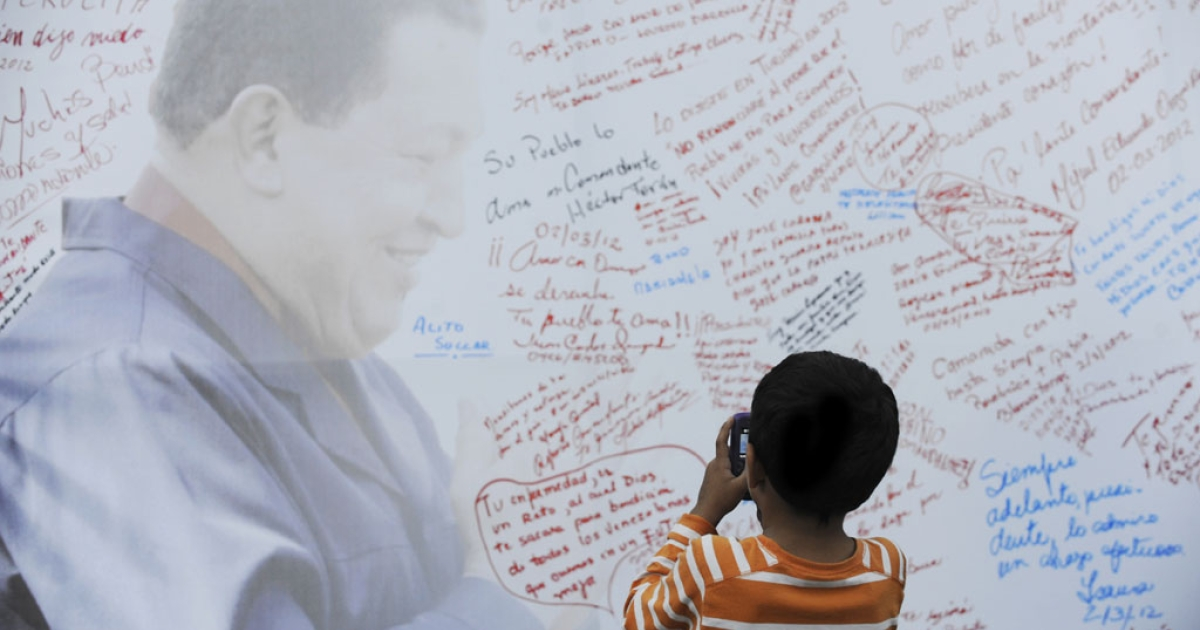 A boy takes pictures of a poster with the image of Venezuelan President Hugo Chavez before Mass at a square in Caracas on March 2. Chavez said he was recovering from surgery in Cuba but will need further radiation treatment.</p>