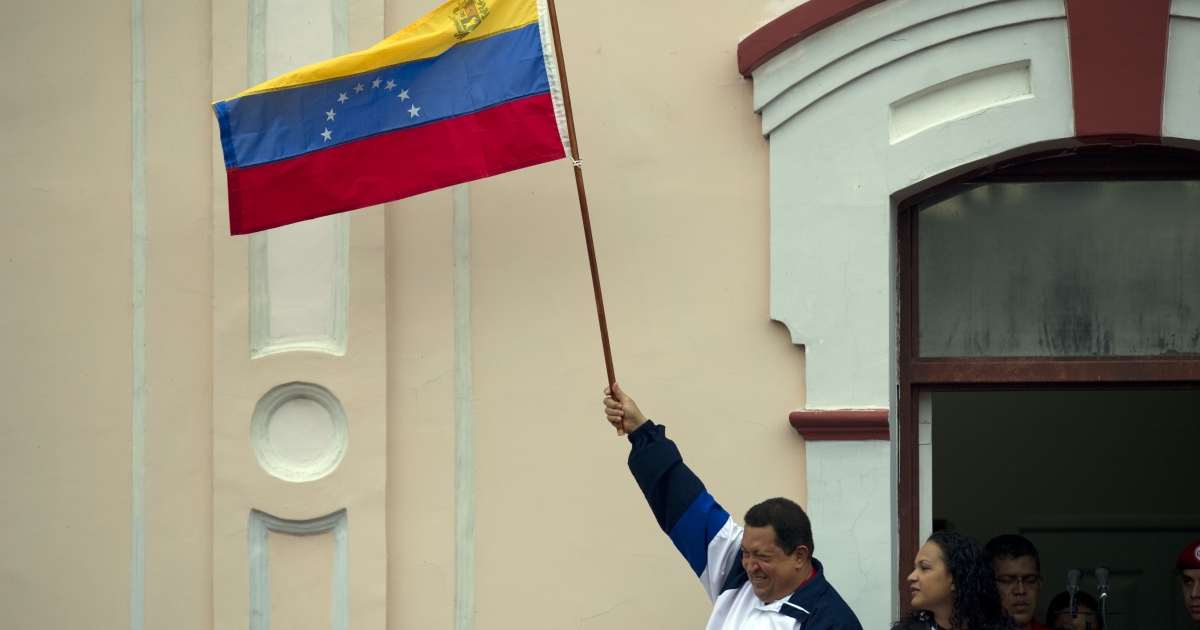 Hugo Chavez, accompanied by his daughter Rosa Virginia, waves a Venezuelan national flag at a balcony of Miraflores presidential palace in Caracas on April 13.</p>