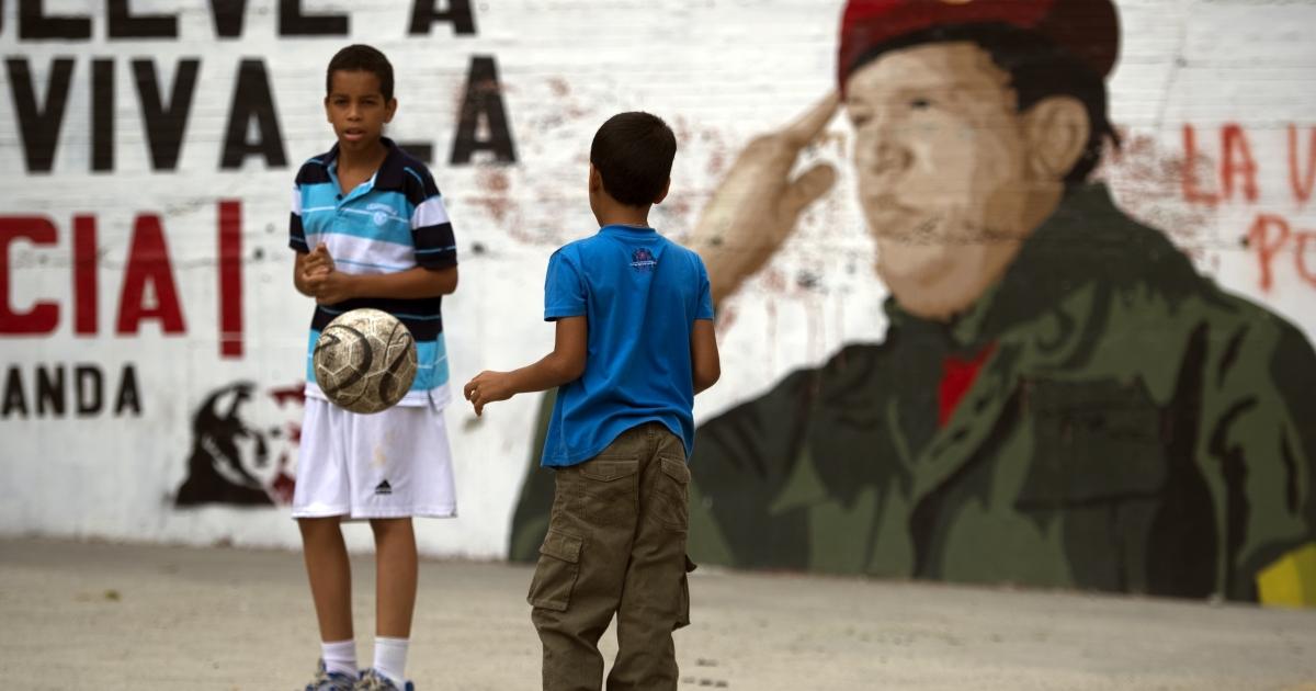 Two children play soccer near a mural of Venezuelan President Hugo Chavez in Caracas.</p>