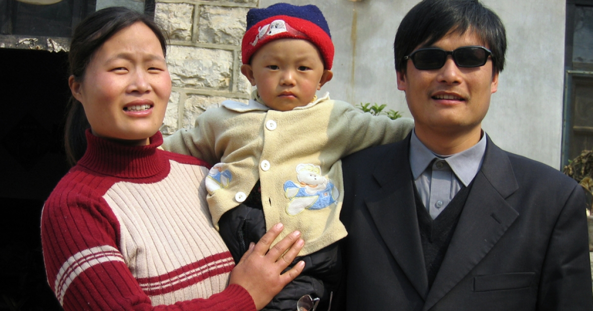 Blind activist Chen Guangcheng with his wife and son outside the home in northeast China's Shandong province, March 28, 2005.</p>