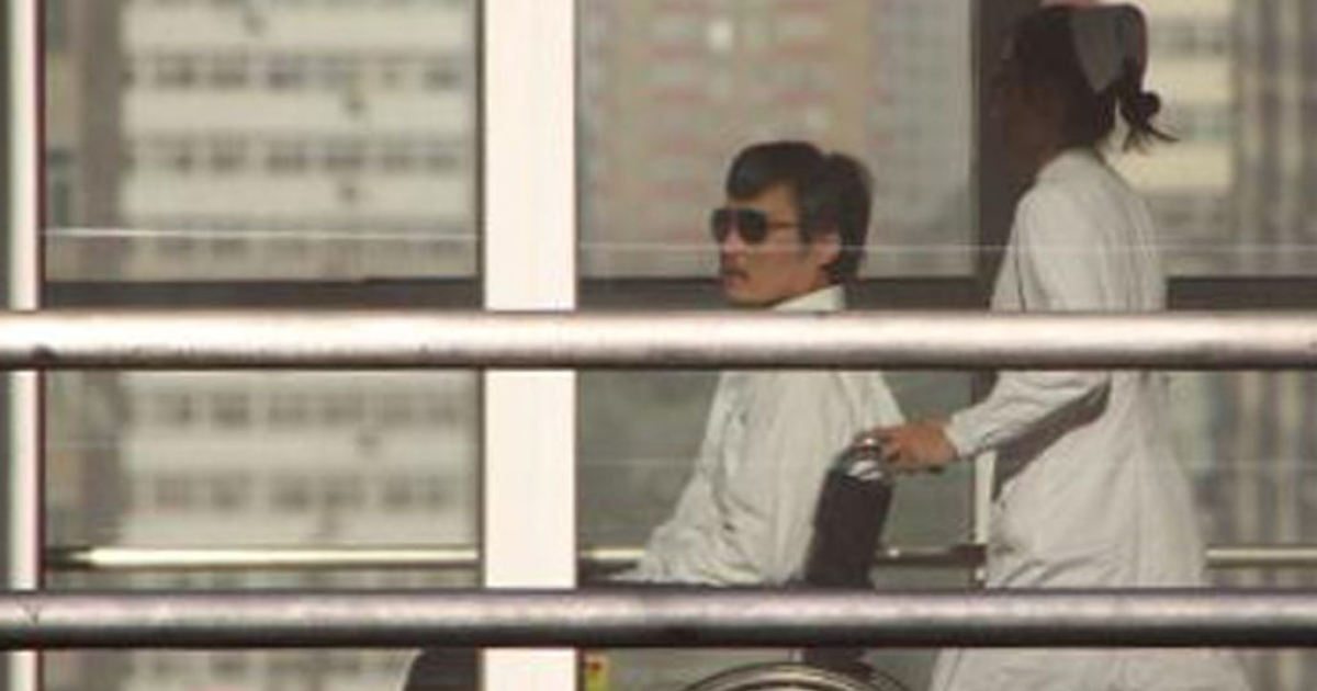 Chinese activist activist Chen Guangcheng is seen in a wheelchair pushed by a nurse at the Chaoyang hospital in Beijing on May 2, 2012.</p>