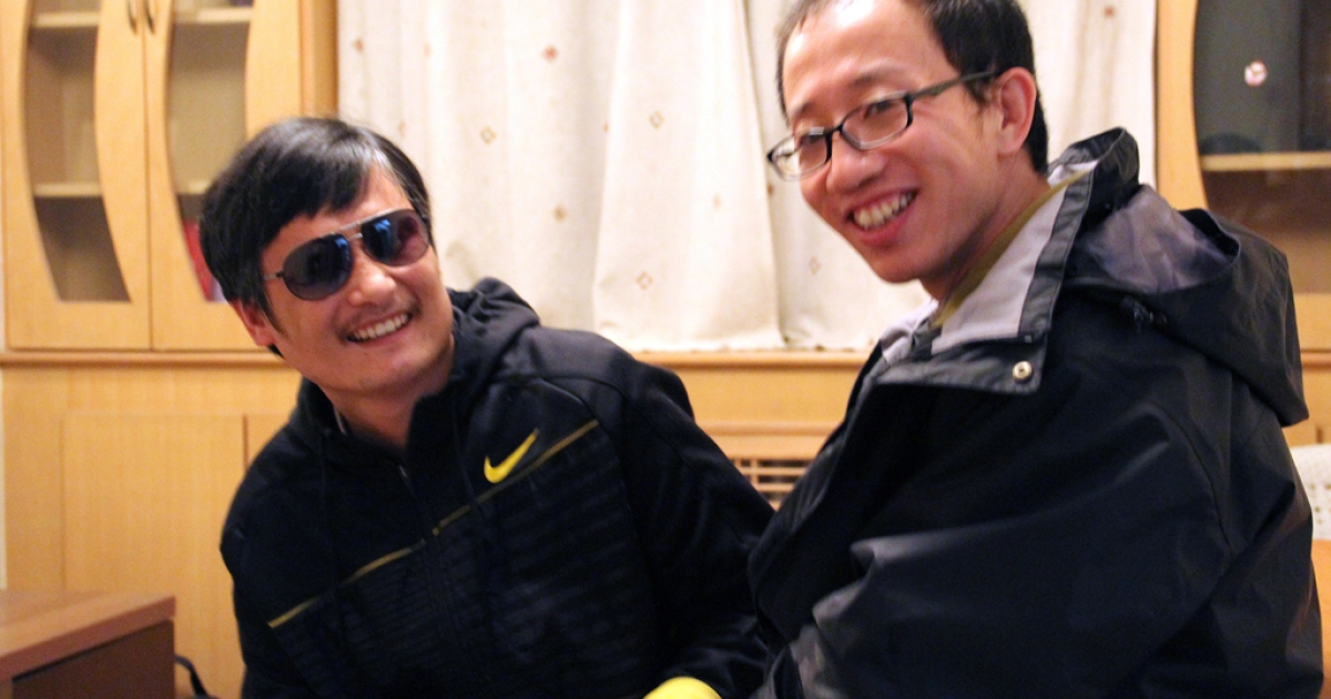 This undated photo shows outspoken government critic Hu Jia (R) sharing a light moment with blind lawyer Chen Guangcheng after his escape, at an undisclosed location in Beijing. Fugitive Chinese activist Chen Guangcheng, who pulled off a daring escape from house arrest, was likely holed up in the US embassy in Beijing, another top dissident said on April 28, 2012.</p>