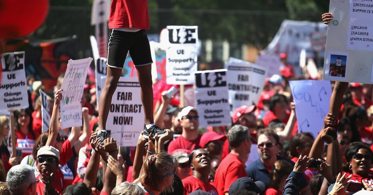 Striking Chicago teachers and their supporters attend a rally at Union Park September 15, 2012 in Chicago, Illinois. An estimated 25,000 people gathered in the park in a show of solidarity as negotiations on a labor contract continue.</p>