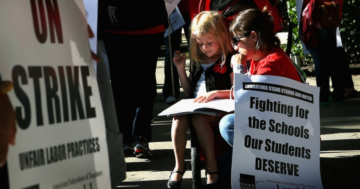 Teacher Jillian Connolly helps her daughter Mary study math problems while picketing on September 10, 2012 in Chicago, Illinois.</p>