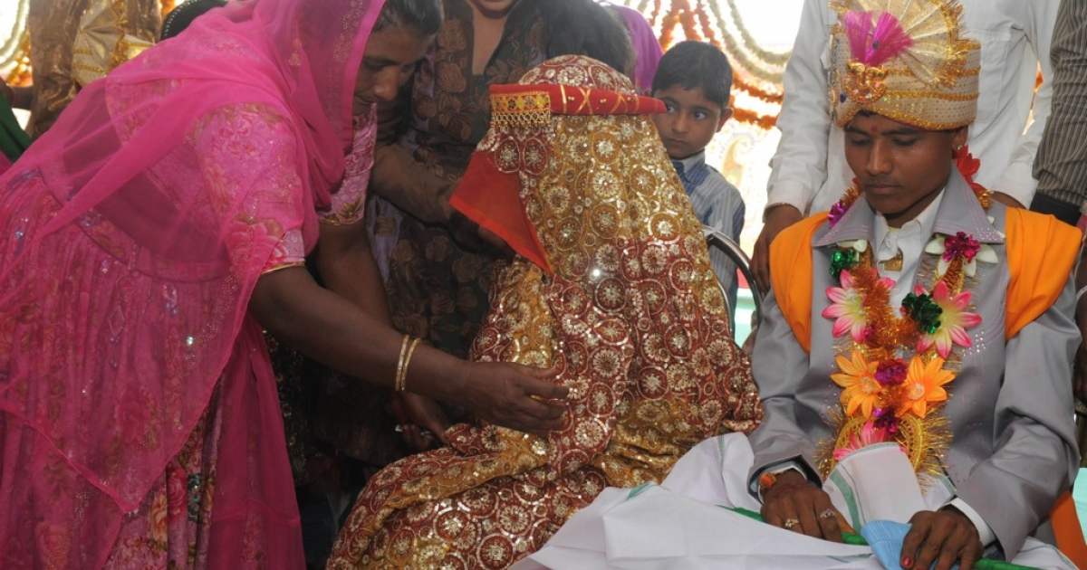A relative (L) comforts a bride as she participates in a mass marriage in the village of Vadia, some 210kms north of Ahmedabad late March 11, 2012.</p>