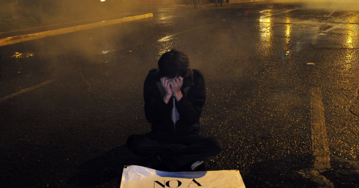 A protester crouches by a sign that reads